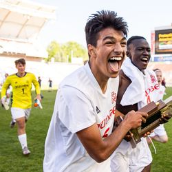 Judge Memorial's Constantine Daskalakis and Emmanuel Okongo carry the trophy as they celebrate their win over Morgan in the 3A boys soccer championship at Rio Tinto Stadium in Sandy on Tuesday, May 18, 2021.