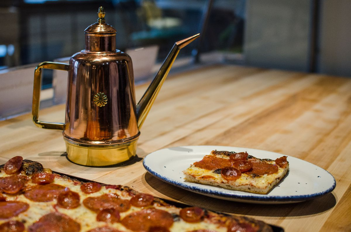 A slice of Roman-style pepperoni pizza sits on a white plate on a wooden counter, next to a pan of pizza that it was cut from. A decorative brass olive oil container is also on the counter.