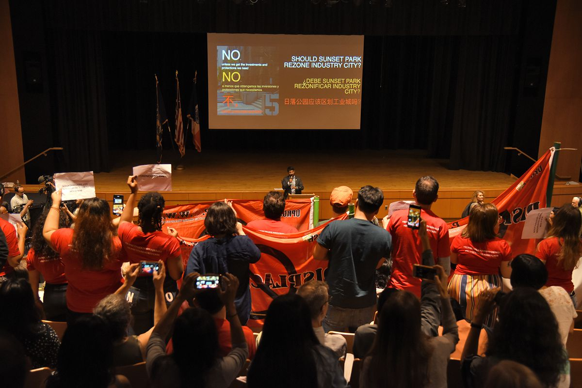 """Protestors holding up """"displacement"""" banners and signs in front of City Councilmember Carlos Menchaca, who is a standing at a podium, in a school auditorium. On the projector behind him a slide reads, """"Should Sunset Park rezone Industry City?"""""""