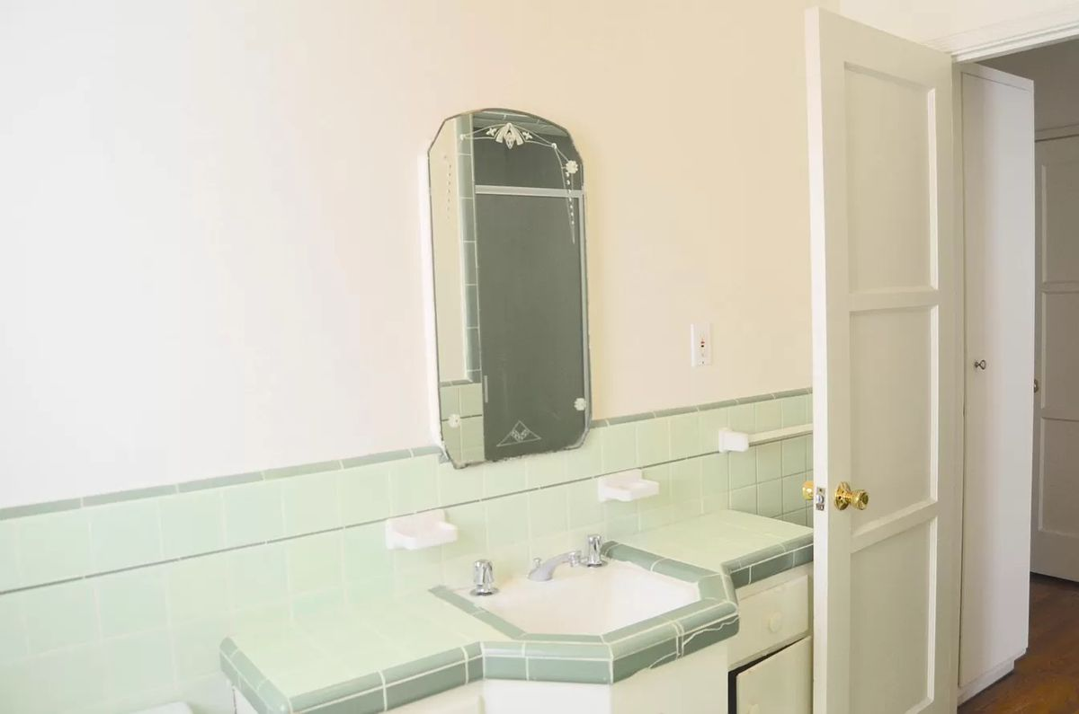 A bathroom with a green tile vanity and white walls