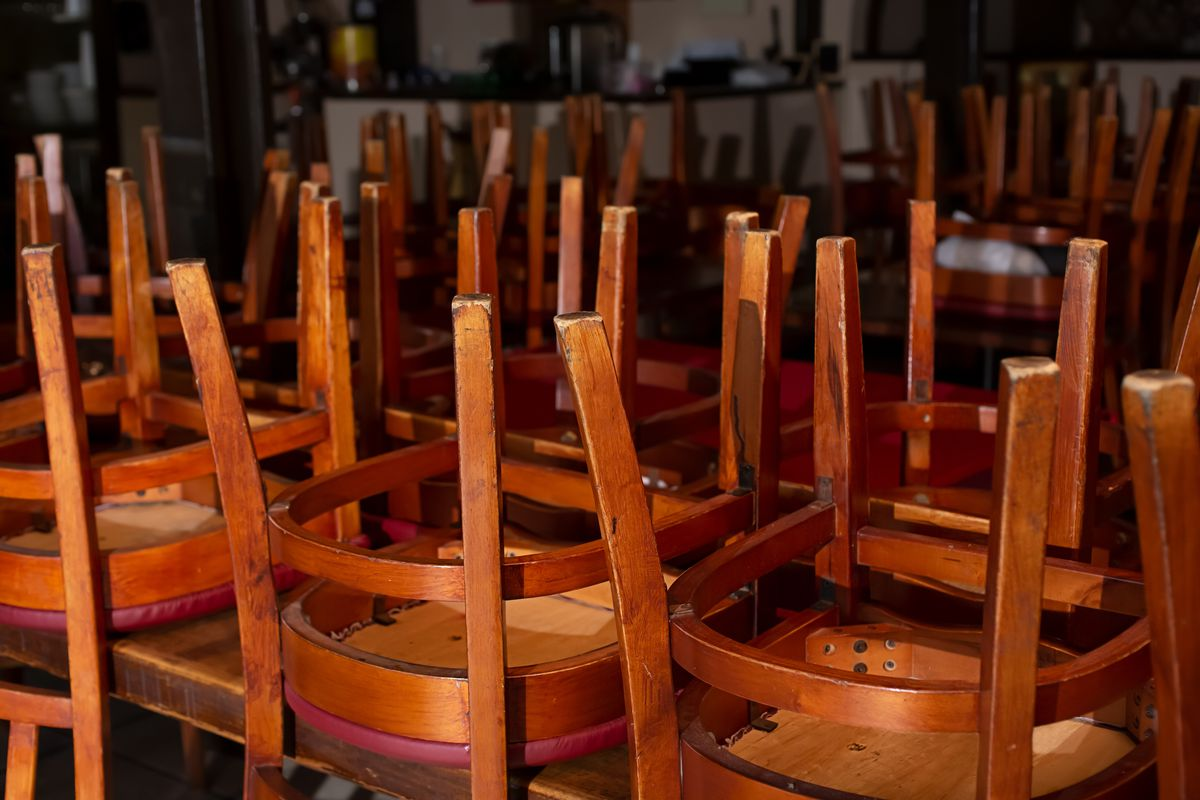 A view of a closed restaurant dining room, featuring all of the chairs turned over on the tables.