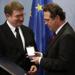 Frankfurt airport employee Lamar Joseph Connor, left, from Altha, Florida, is awarded with The Cross  of Merit of the Federal Republic of Germany by Gernan Intrerior Minister Hans-Peter Friedrich in Berlin, Germany, Monday, Jan. 16, 2012. Interior Minister Hans-Peter Friedrich  honored two Americans for helping apprehend an Islamic extremist who attacked a U.S. Air Force bus last year and killed two airmen. Staff Sgt. Trevor Brewer and  Lamar Joseph Conner a civilian airport employee, both of whom chased the suspect after the March 2 shooting, helping police arrest him at the scene.  Arid Uka, a 21-year-old Kosovo Albanian, is currently on trial for the slayings and has admitted to the charges. He faces up to life in prison, and a verdict and sentence are expected Thursday.  Brewer  said he was on the bus when Uka began shooting. The Tennessee native said Uka pointed a pistol at his head and pulled the trigger, but it jammed and didn't fire.