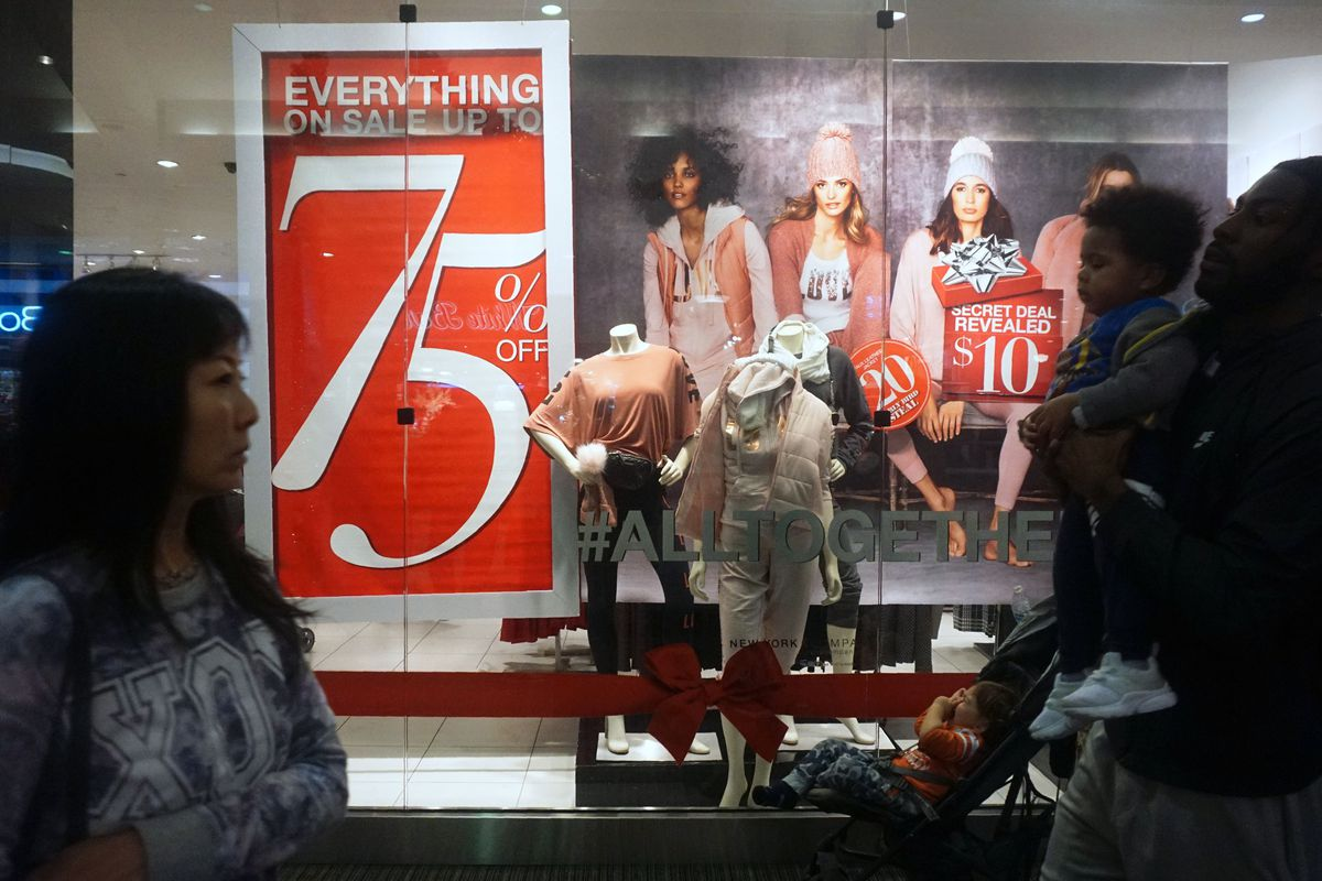 """People walk past a clothing store window featuring mannequins and a sign advertising """"Everything 75% off."""""""