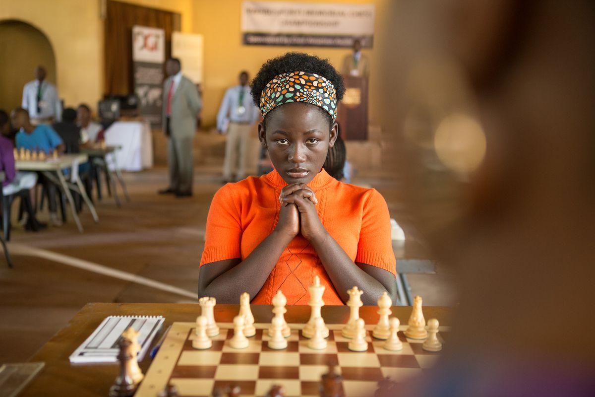 Madina Nalwanga plays Phiona Mutesi, concentrating hard at the chess board.