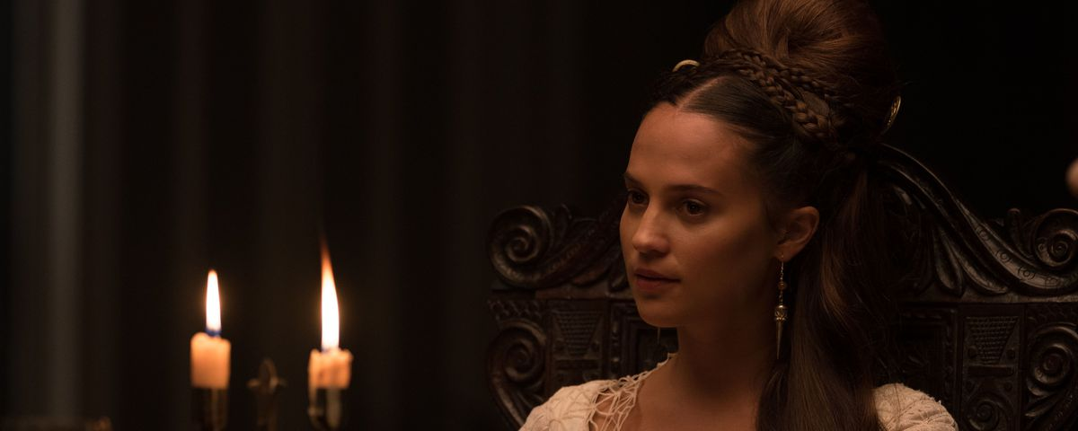 Alicia Vikander as a richly dressed noble lady at a banquet feast gives Gawain a good eyeing-up in The Green Knight
