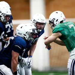 BYU quarterback Beau Hoge calls out a play in the huddle during the Cougars' practice in the Indoor Practice Facility on Thursday, March 15, 2018 in Provo.