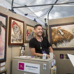 """Michael Rohner laughs with customers while talking about the squid in one of his pieces on the first day of the Utah Arts Festival in Salt Lake City on Thursday, June 22, 2017. Rohner describes his art as """"gently confrontational"""" because he tries to evoke emotions from his audiences with his work."""
