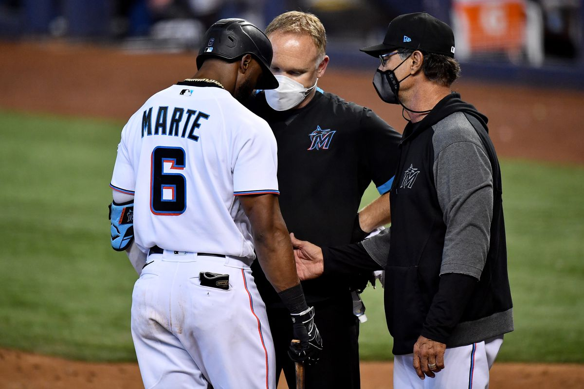 Don Mattingly #8 pulls Starling Marte #6 of the Miami Marlins from the game due to injury in the ninth inning against the San Francisco Giants at loanDepot park on April 18, 2021 in Miami, Florida.