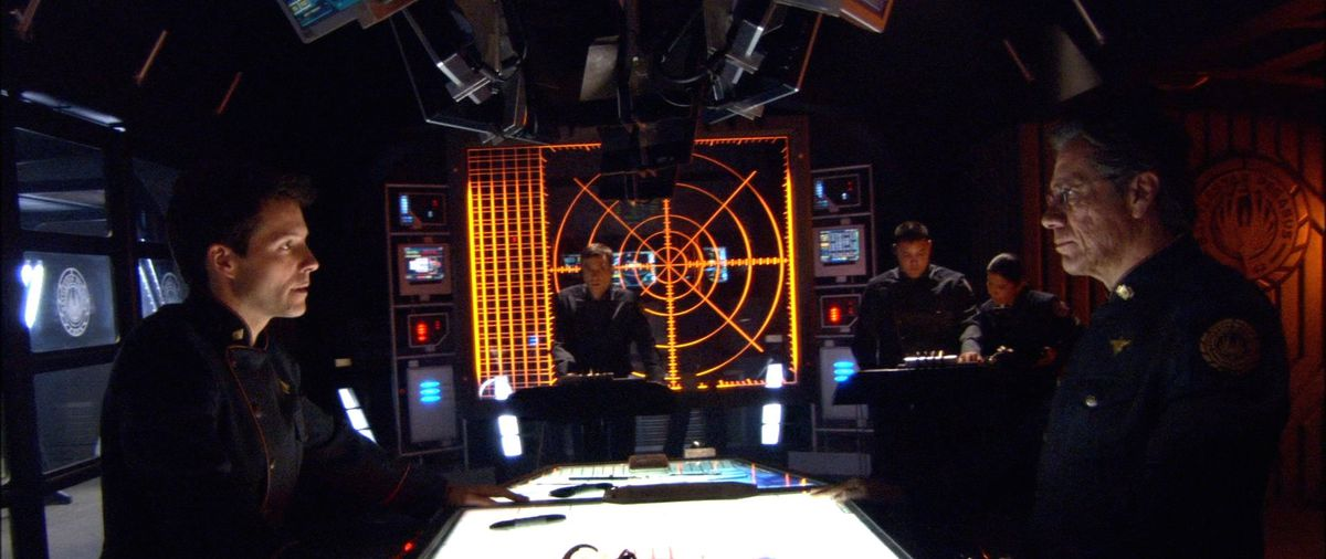 William and Lee Adama face each other grimly across a lighted table in a dark room in Battlestar Galactica