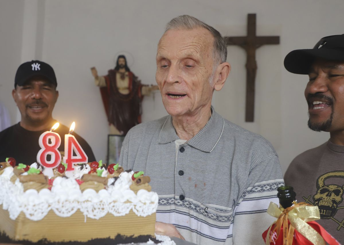 In Dili, East Timor, defrocked Catholic priest Richard Daschbach (center) is presented a cake on Jan. 26 for his 84th birthday.