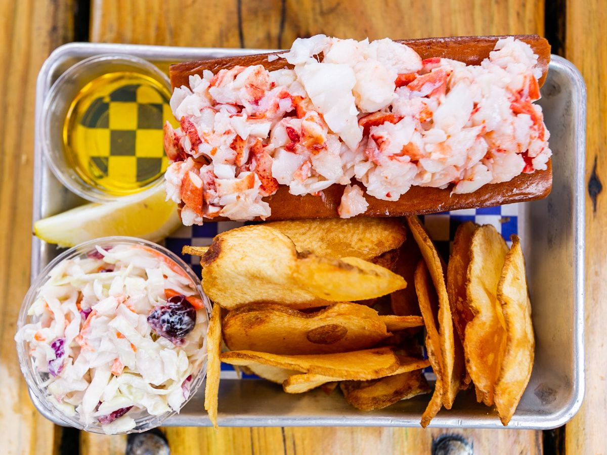 A lobster roll, chips, cole slaw, and drawn butter on an aluminum tray