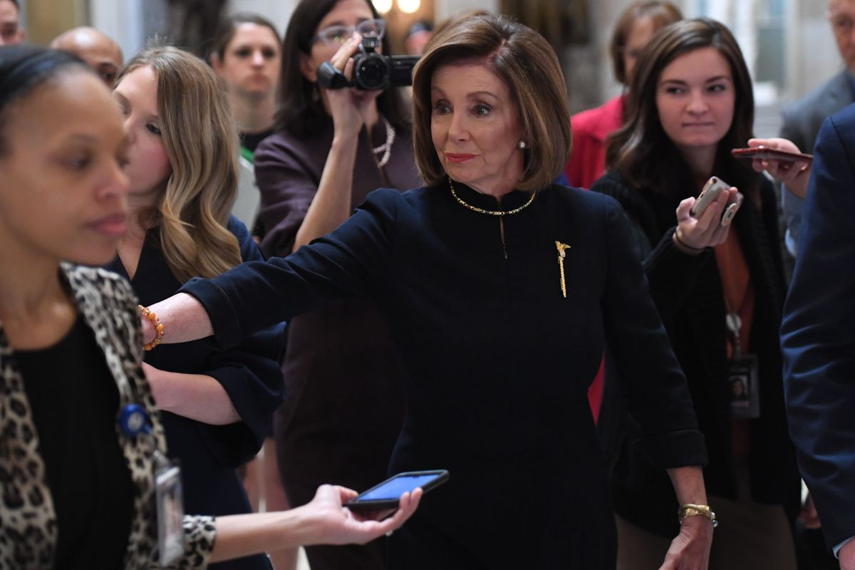 Speaker of the House Nancy Pelosi walks to the House floor, while the House readies for a historic impeachment vote.