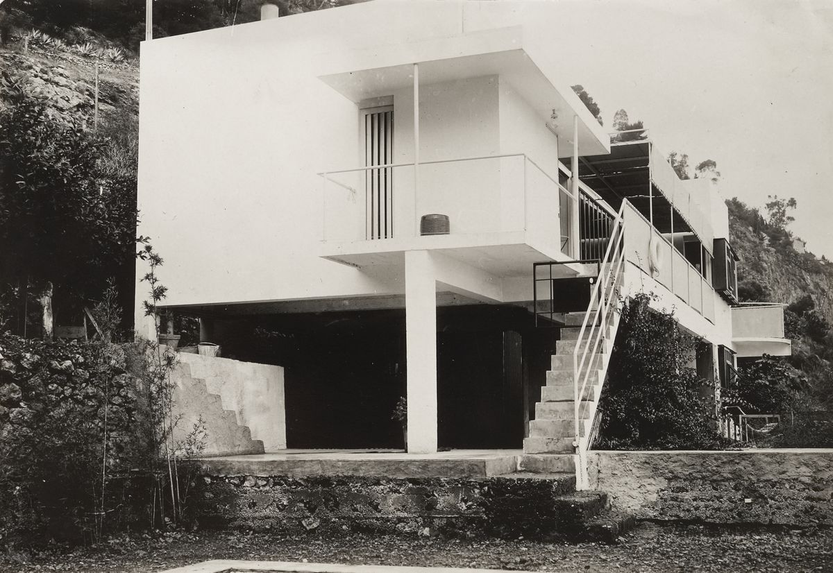 Black and white photo of the side of a modern building featuring a steep and narrow staircase.