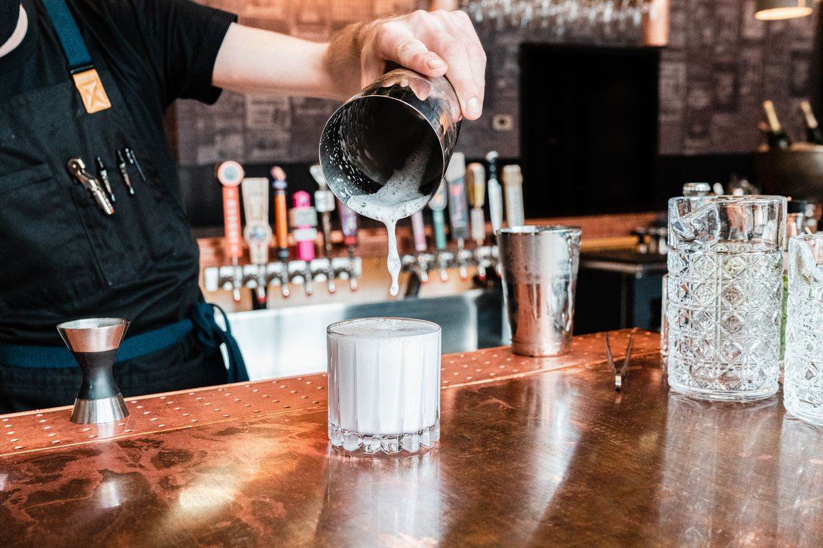 A bartender pours a frothy drink into a lowball glass from a silver tin shaker.