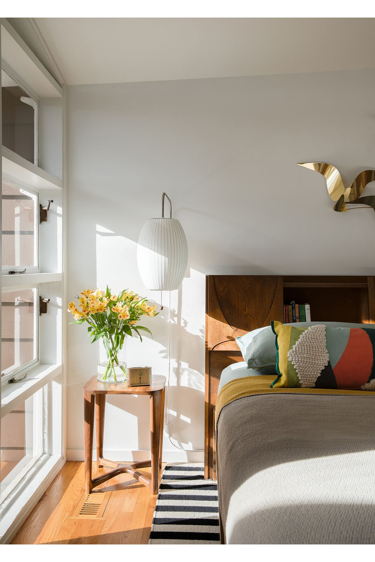 A bedroom. There is a bed with grey bed linens and multiple patterned pillows. Next to the bed is an end table with a vase with yellow flowers. One of the walls is comprised of floor to ceiling windows letting in outside light.