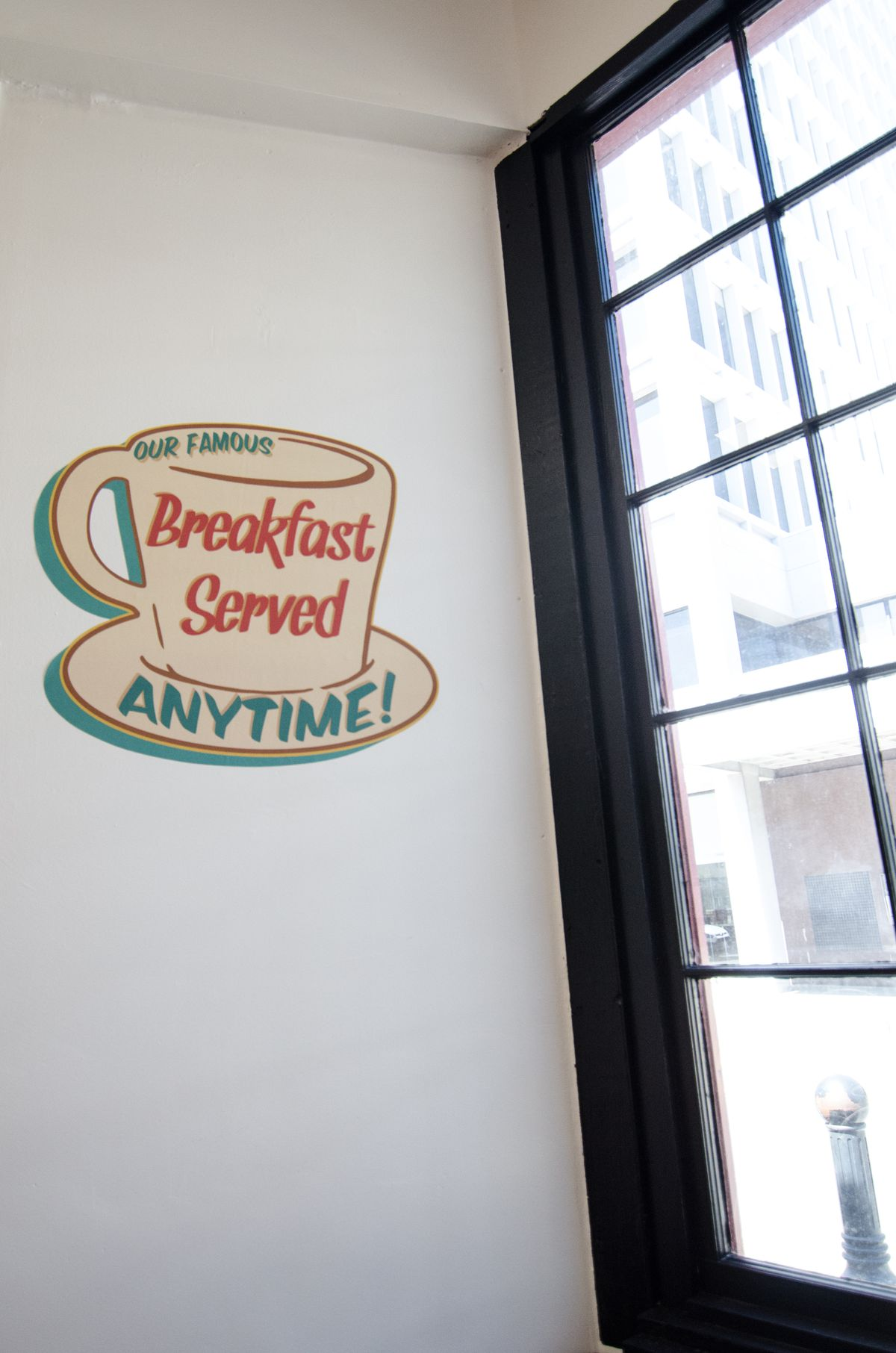 """A coffee cup-shaped vintage sign says """"Our famous breakfast served anytime!"""" and hangs on a white wall near a window"""
