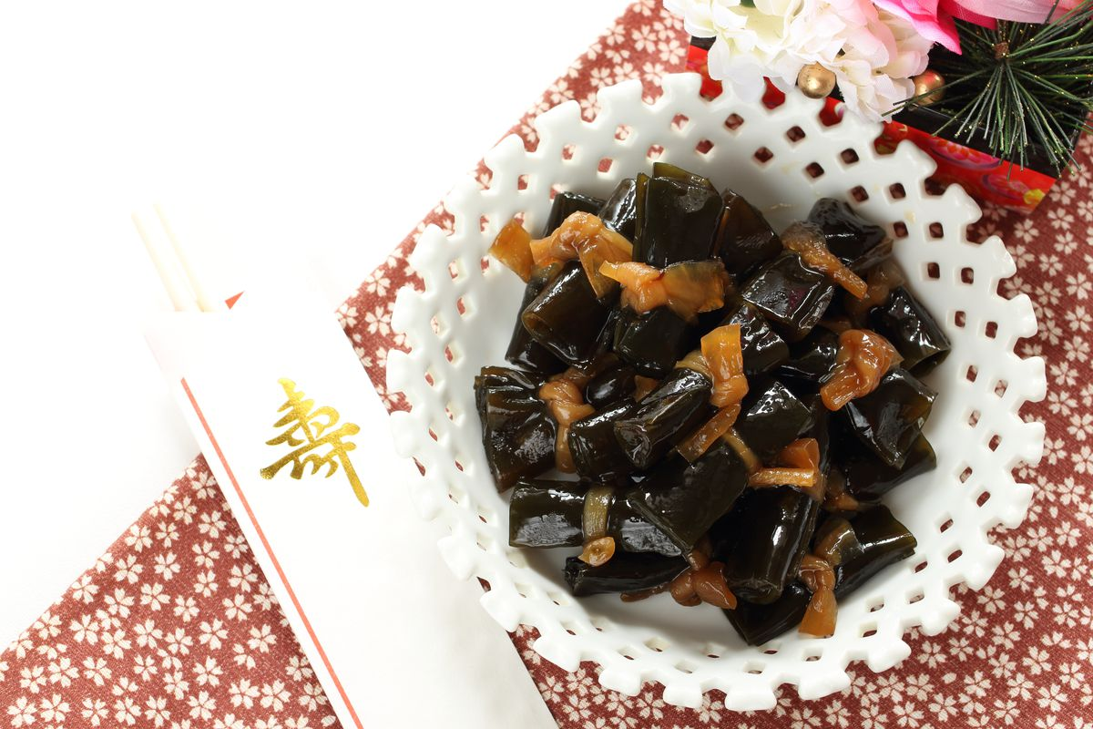 Braised kelp leaves wrap around small bites of pork in a white bowl.