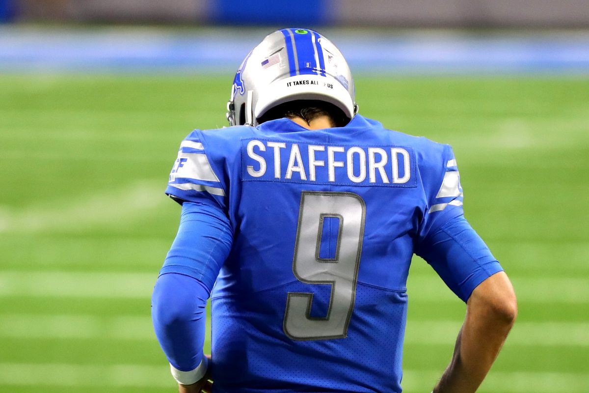 Matthew Stafford #9 of the Detroit Lions grabs his side after being tackled during the fourth quarter against the Green Bay Packers at Ford Field on December 13, 2020 in Detroit, Michigan.
