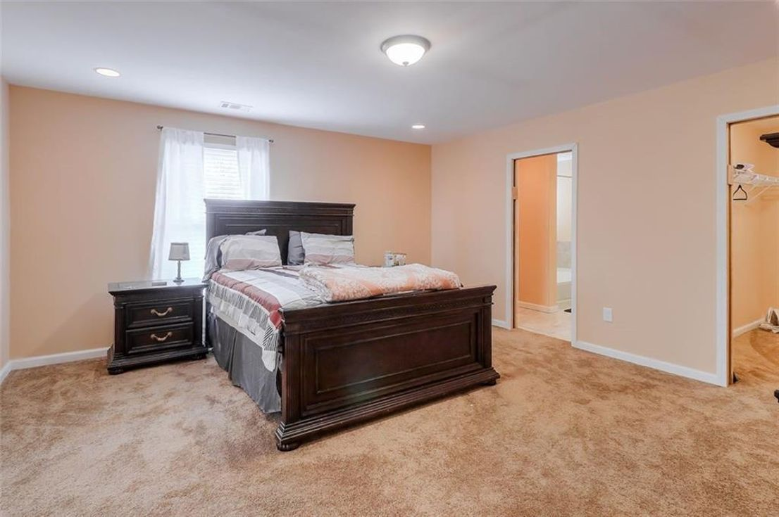 A large pink bedroom with carpeting and a big wood bed.