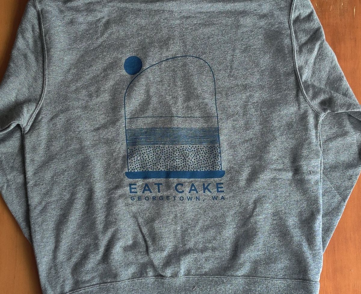 """A gray hoodie with the Deep Sea Sugar and Salt logo and """"Eat Cake: Georgetown, WA"""" written below"""