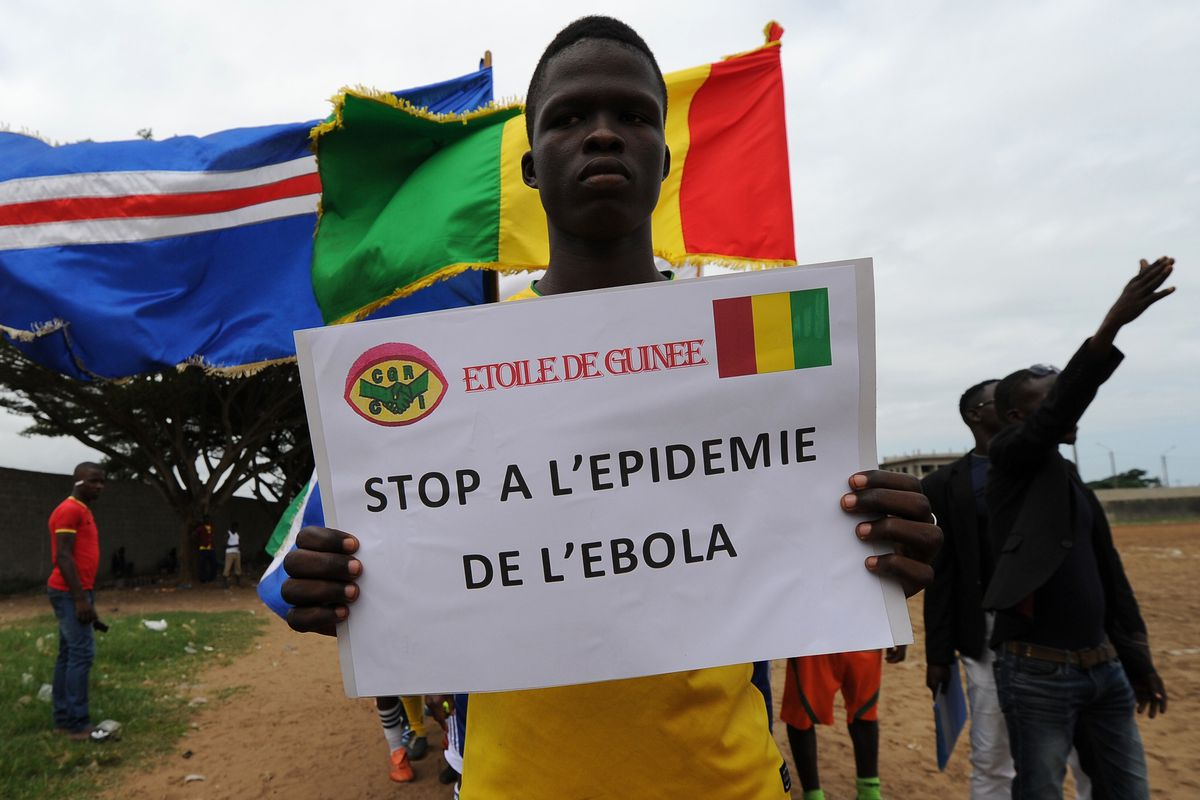 Players of the ''L'Etoile de Guinee'' football team poses with a sign reading ''Stop to the ebola epidemic'' prior to a football tournament gathering youth from Guinea near the Koumassi sports center in Abidjan on August 10, 2014.