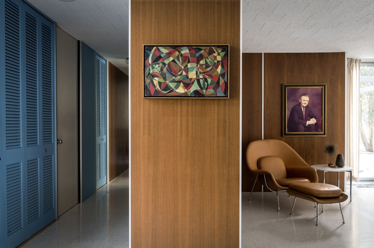 A shot looking down the hall and into the living room. You see blue closet doors and a brown-leather Womb chair.