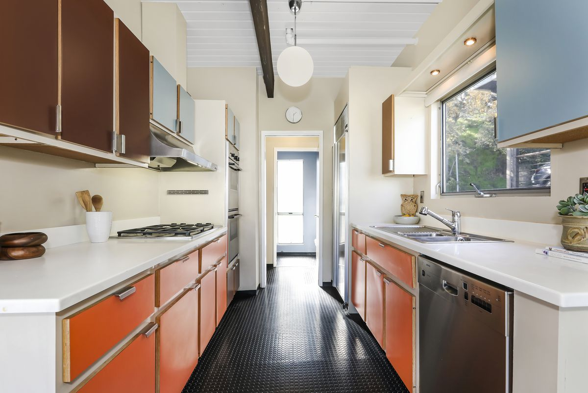 A galley kitchen with orange, brown, and blue-colored cabinets. The countertops are white and the dishwasher and oven are stainless steel.