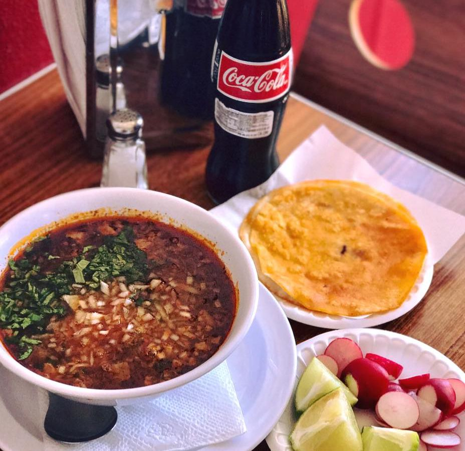 A bowl of birria, Tijuana-style shredded beef stew with a tortilla and Mexican Coke.