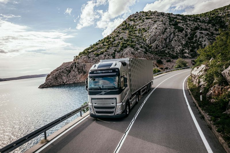 A Volvo electric truck driving on a coastal road backed by rocky hills.