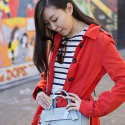 """Sona's preppy look pops thanks to the contrast between her red jacket and light blue bag. She's wearing an H&M jacket and dress, Gap sunglasses, a Coach purse, and a <a href=""""http://www.brandypham.com"""">Brandy Pham ring."""