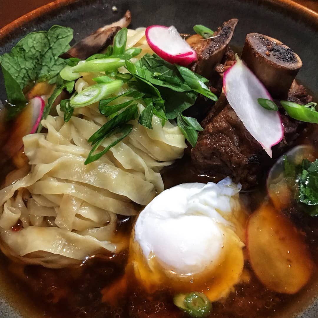 Closeup of a ramen bowl with thick noodles, egg, and oxtail
