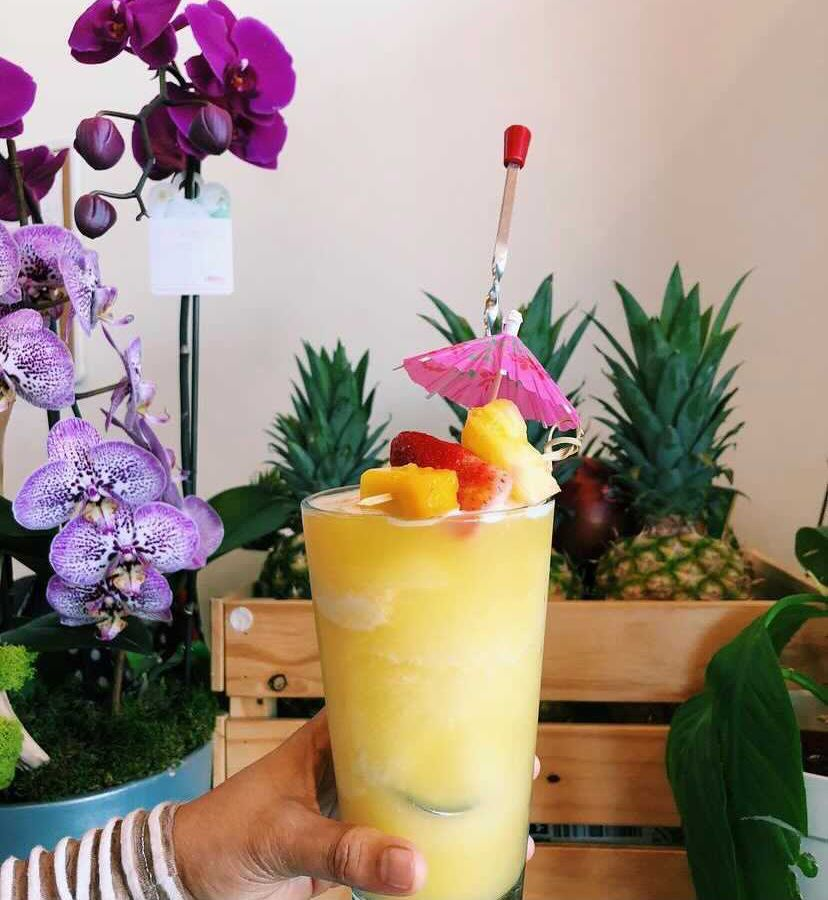 Hand holding a colorful summer cocktail