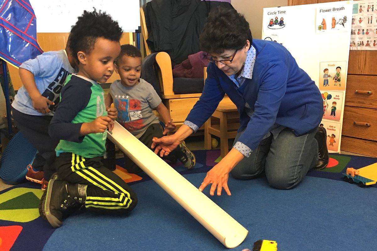 Sheryl Robledo, an early childhood coach, plays with preschool students at a Sewall Child Development Center site in far northeast Denver.
