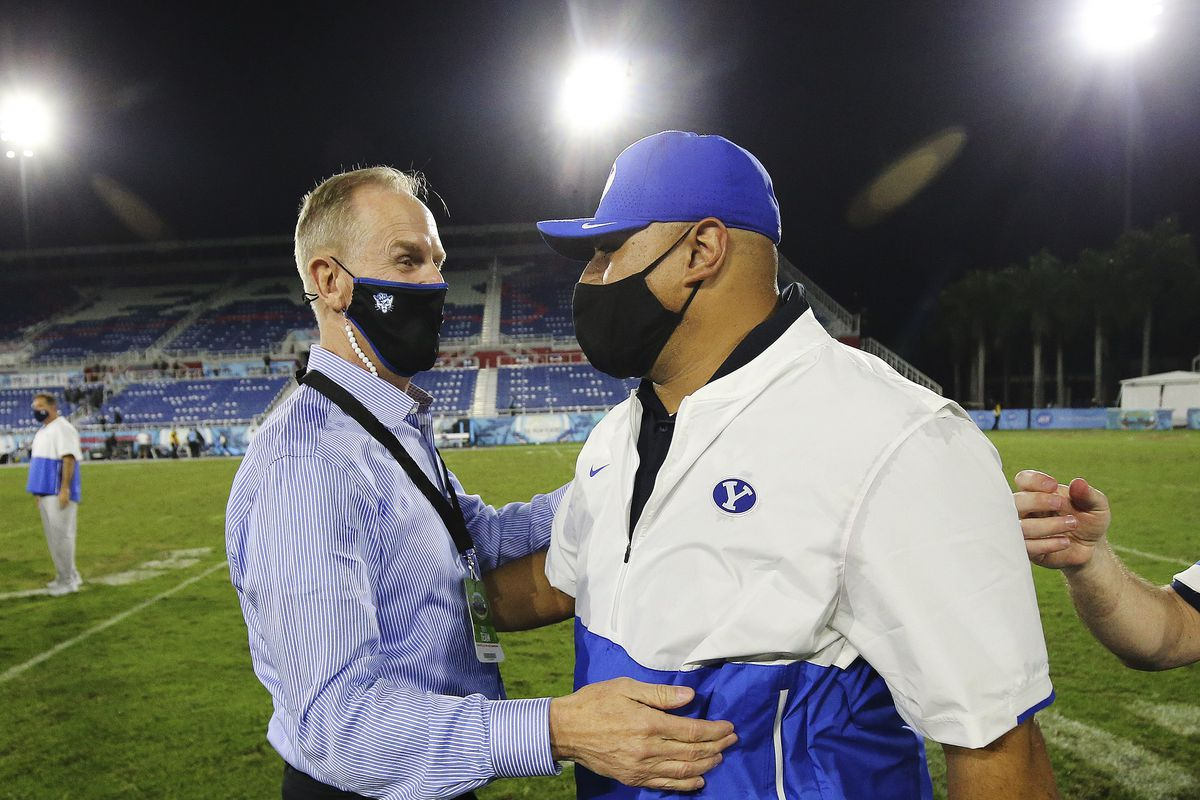 BYU athletic director Tom Holmoe hugs Football coach Kalani Sitake to celebrate a win at the Boca Raton Bowl. They are wearing black masks and are on a football field.