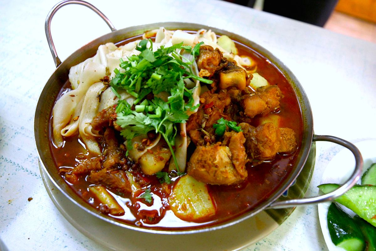 A big metal bowl with stewed chicken and noodles, topped with a pile of cilantro