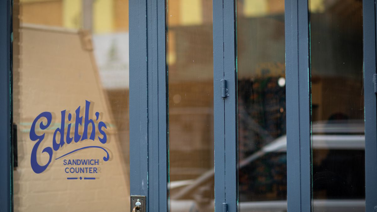 """A storefront with the words """"Edith's sandwich counter"""" is papered over from the inside"""