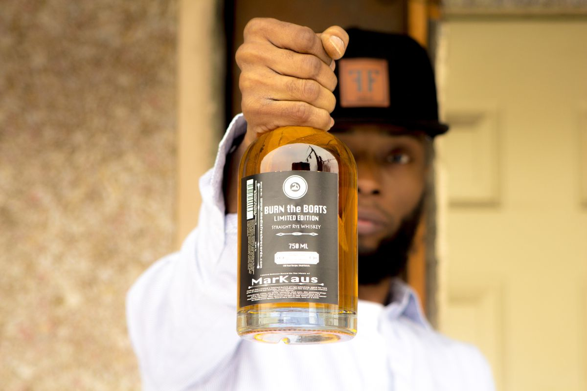Man holds a bottle of whiskey.