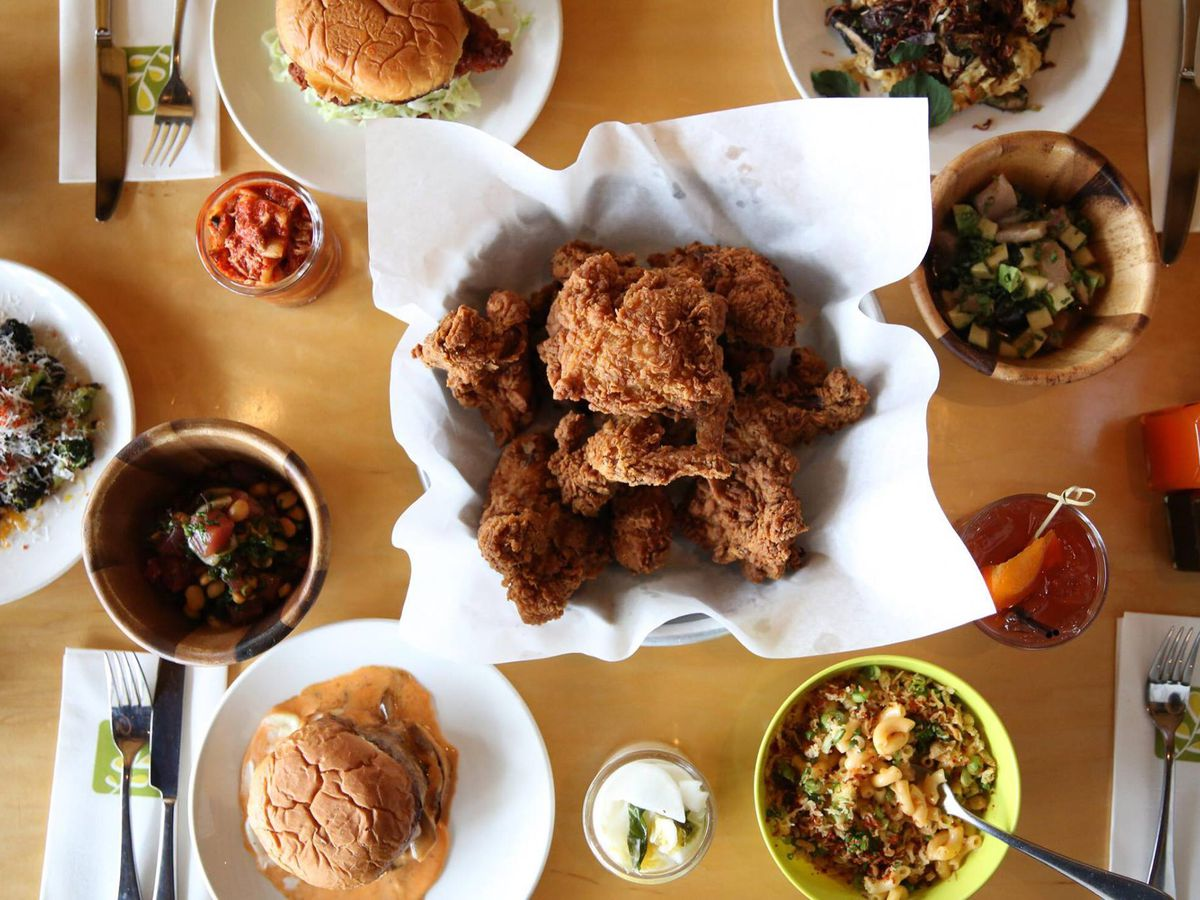 Top-down view of a plate of Ma'ono's fried chicken surrounded by an array of sides.