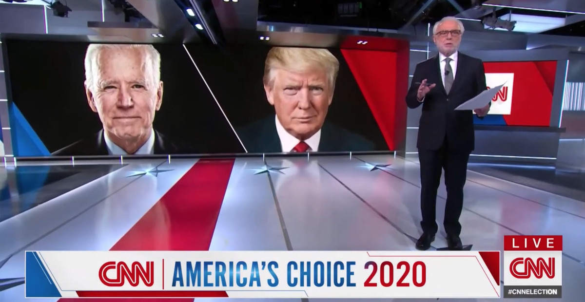 Wolf Blitzer before an image of Joe Biden and Donald Trump on election night