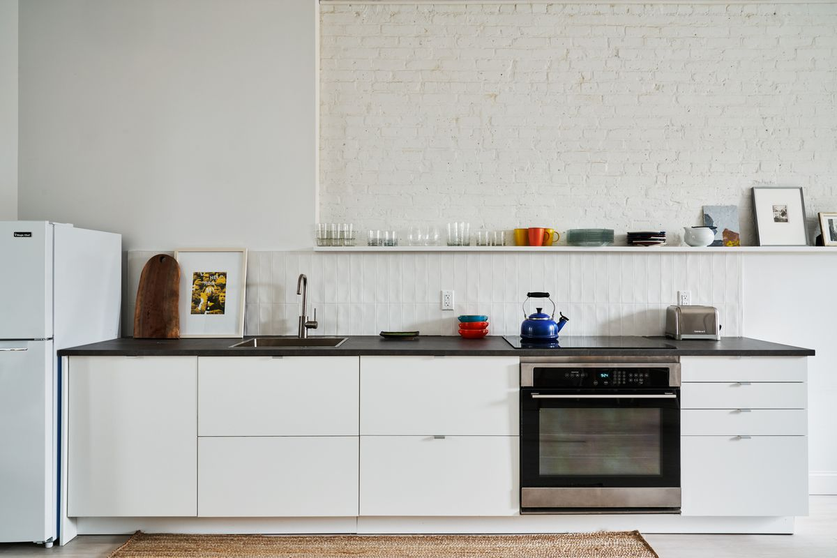 A kitchen with exposed white brick and white cabinetry.