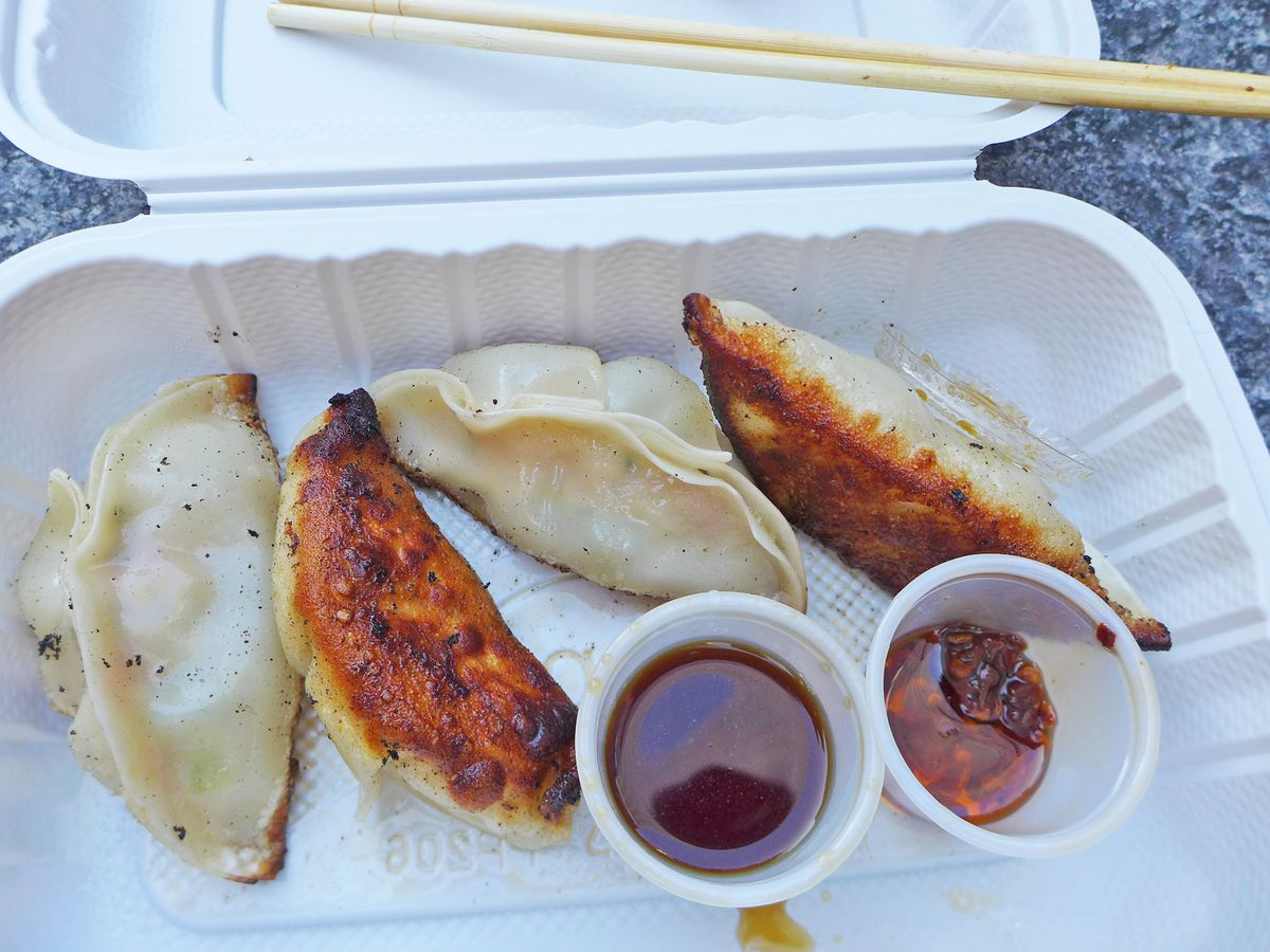 Four oblong ridged dumplings with browned bottoms and two dipping sauces, soy and chile oil.