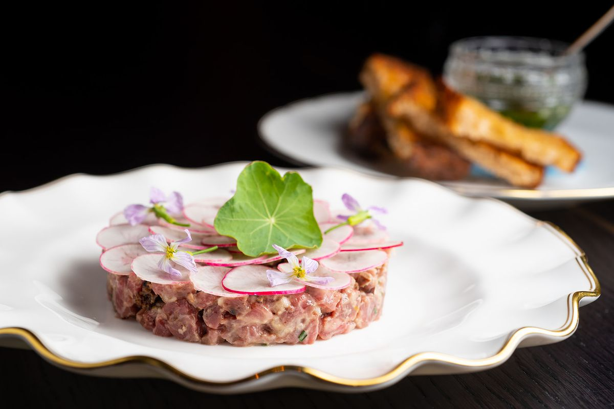 A plate of beef tartare with radishes on top and nasturtium.