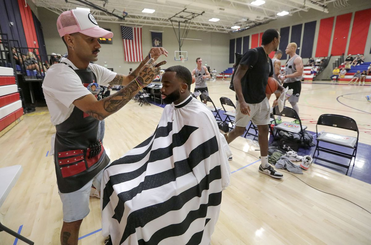J.T. Davis brings his Pacific Kuts Barbershop skills to the sidelines and cuts Lou Mayela's hair during a Powder League basketball game at American Preparatory Academy in Draper on Friday, June 25, 2021.