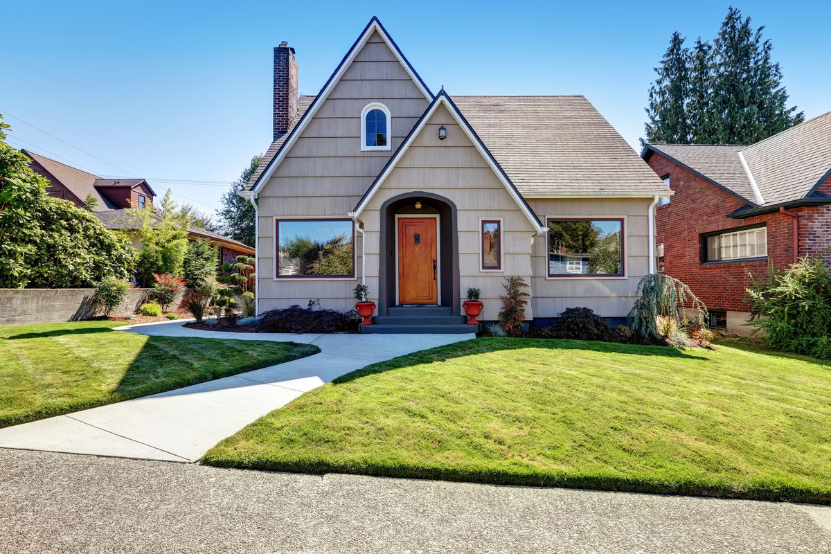 A grey craftsman home with wooden front door, healthy green front yard, and red planters in a downtown district.