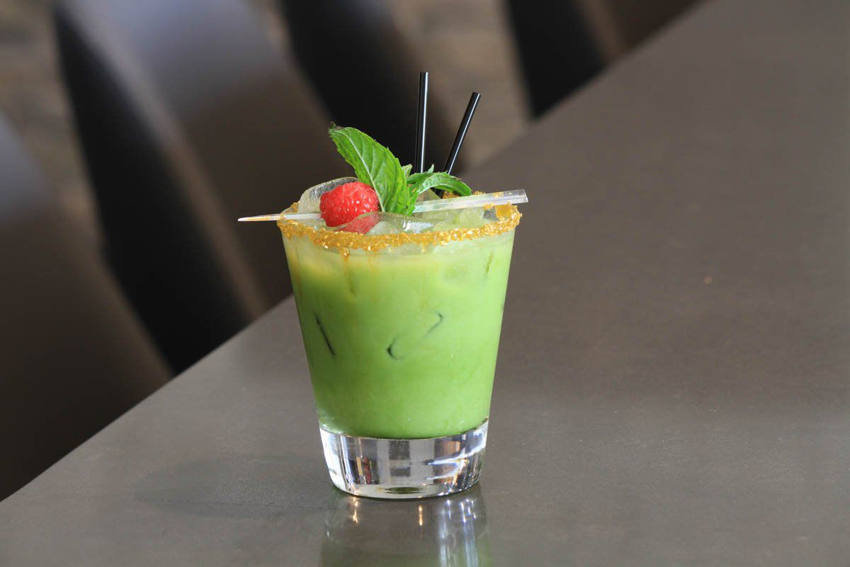 A green cocktail with mint and a raspberry on top