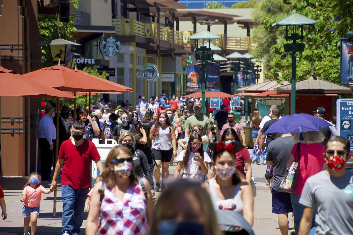 In this July 9, 2020, file photo, guests at the Disneyland Resort visit the Downtown Disney District in Anaheim, Calif.