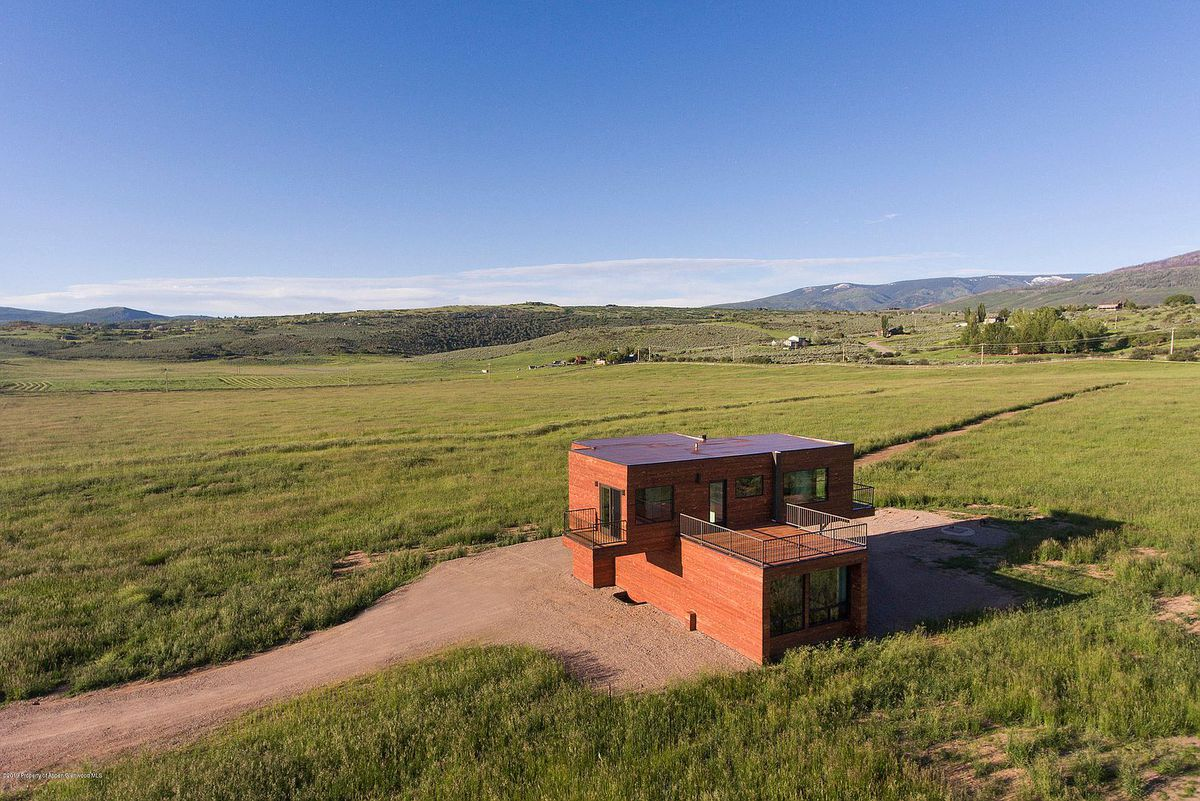 House with multiple decks surrounded by pastures.