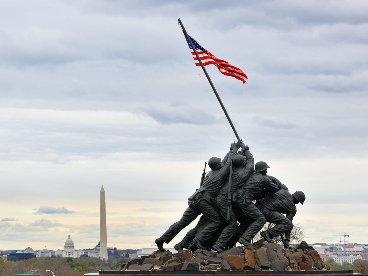 A statue of a group of six soldiers raising an American flag. The Washington Monument and the U.S. Capitol are in the background.