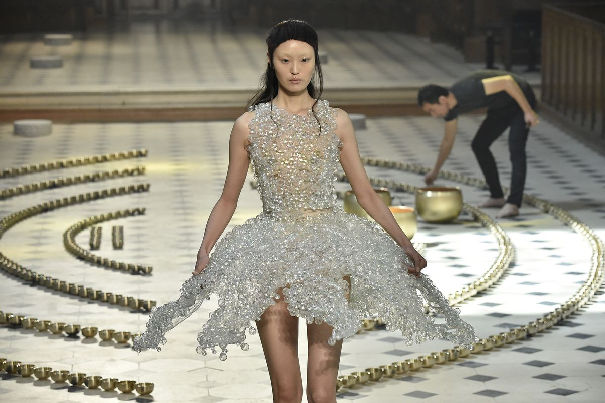 A model walks the runway wearing a dress with a ballerina-like tutu created from thousands of small glass spheres.