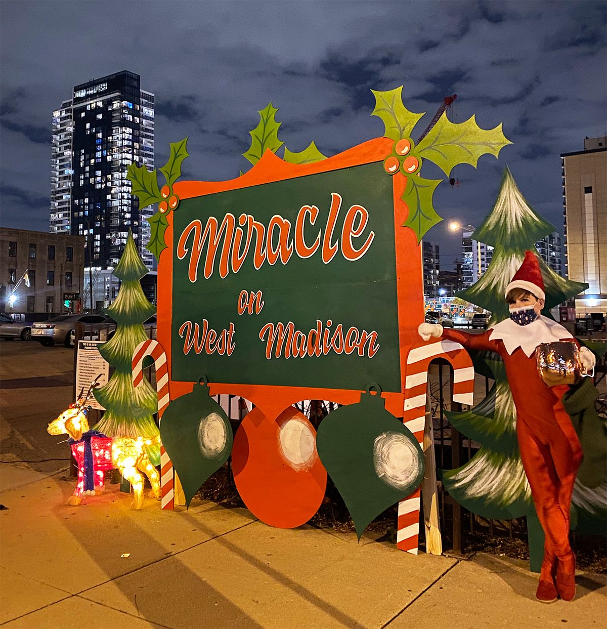 """A person dressed as an elf in a red jumpsuit stands next to a sign decorated with candy canes and Christmas trees. It reads, """"Miracle on West Madison."""""""